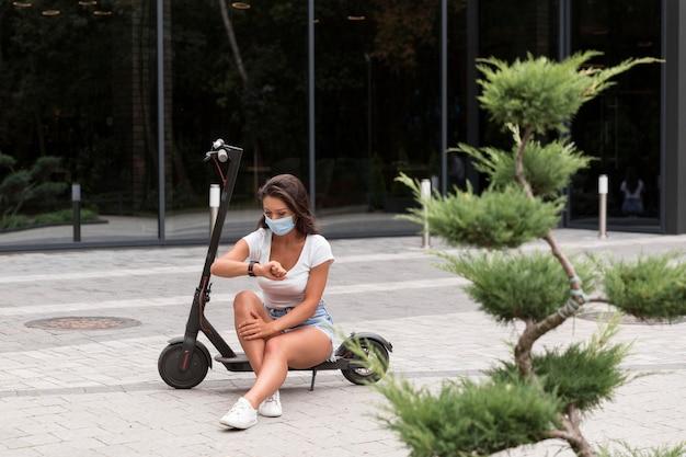 Frau mit der medizinischen maske, die smartwatch neben roller betrachtet