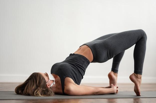 Frau mit der medizinischen maske, die yoga auf matte zu hause tut