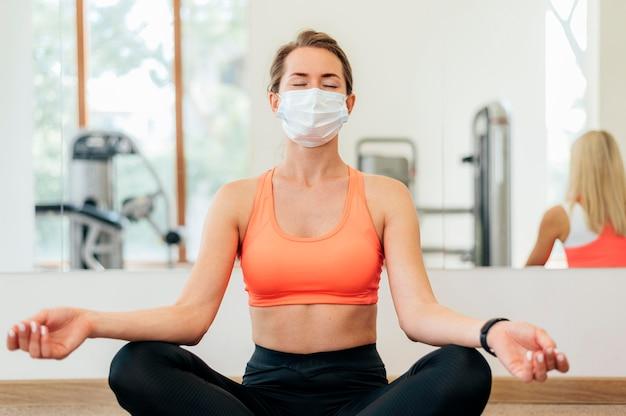 Frau mit der medizinischen maske, die yoga im fitnessstudio tut