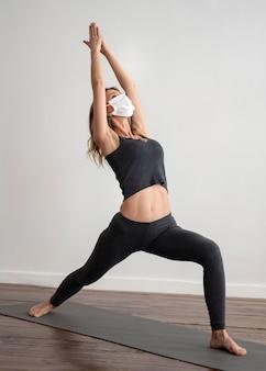 Frau mit der medizinischen maske, die yoga tut