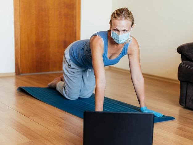 Frau mit der medizinischen maske, die zu hause trainiert