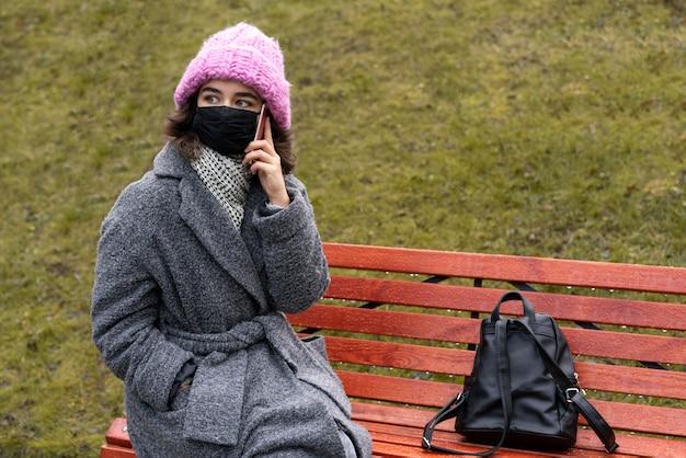 Frau mit der medizinischen maske in der stadt, die über das telefon auf bank unterhält