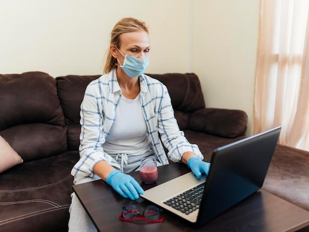 Frau mit der medizinischen maske zu hause, die am laptop arbeitet