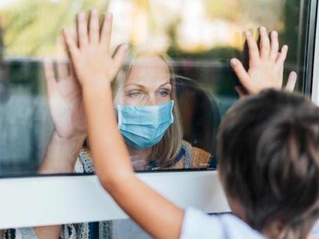 Frau mit der medizinischen maske zu hause, die neffen durch das fenster salutiert