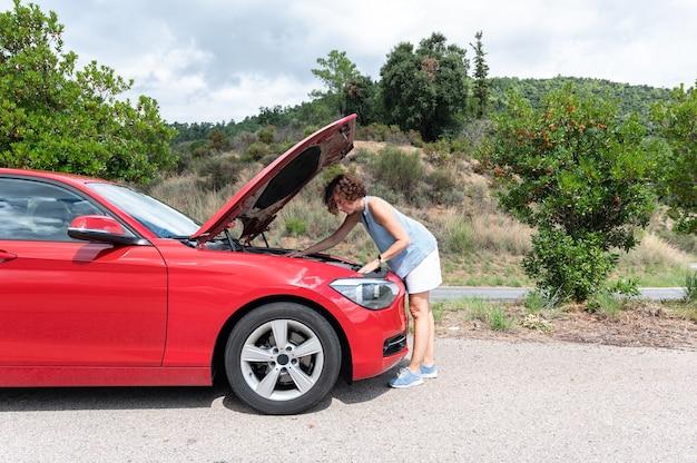 Frau mit der motorhaube ihres autos angehoben, den motor betrachtend