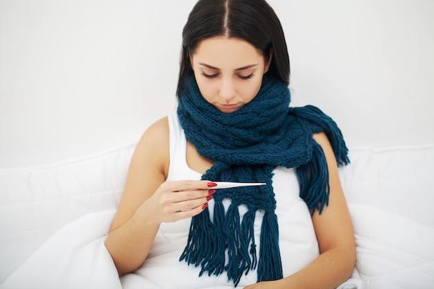 Frau mit der niesenden nase unter verwendung des gewebes auf dem bett, das das kalte grippevirus hat medizin leidet