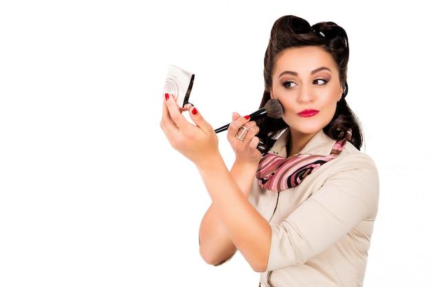 Frau mit der pin-up-frisur, die spiegel hält
