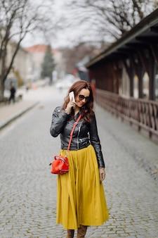 Frau mit der roten handtasche, die beim sprechen am telefon geht