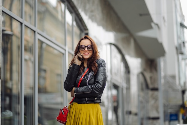 Frau mit der roten handtasche, die beim sprechen am telefon nahe einem geschäftsgebäude geht