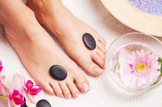 Frau mit der schönen haut der füße und der frischen maniküre, die spa-behandlungen für ihre füße tut.