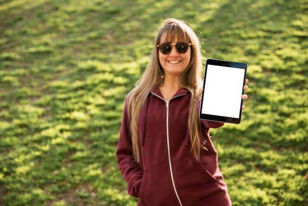 Frau mit der sonnenbrille, die tablette hält