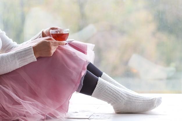 Frau mit der tasse tee die gestrickte strickjacke tragend, die nach hause am fenster sitzt