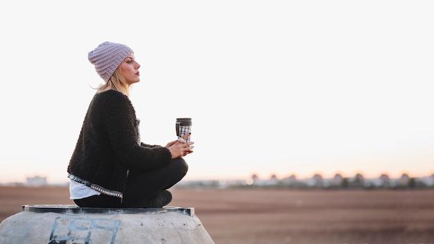 Frau mit der thermosflasche, die in der natur sich entspannt