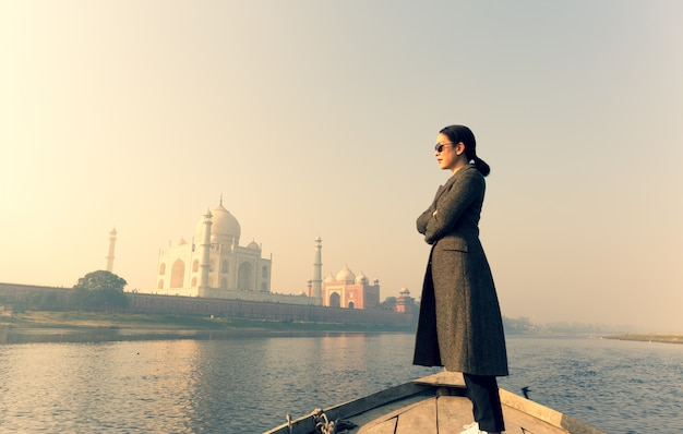 Frau mit der tragenden sonnenbrille, die auf einem boot mit taj mahal im hintergrund steht.