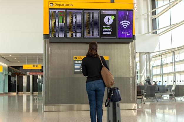 Frau mit der umhängetasche und gepäck, die flugplan im internationalen flughafen betrachten
