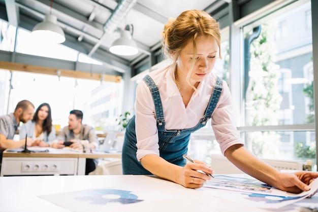 Frau mit diagrammen im modernen büro