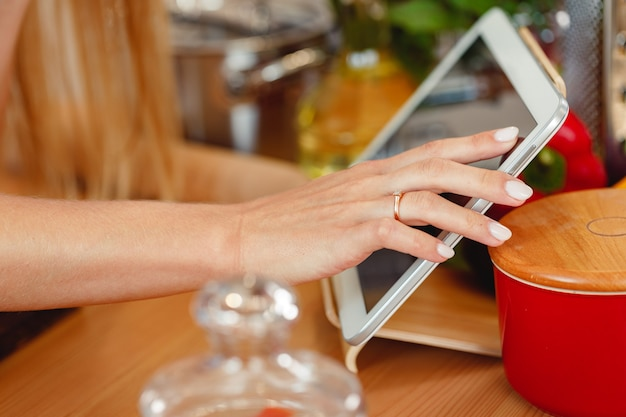 Frau mit digital-tablette beim kochen in der küche