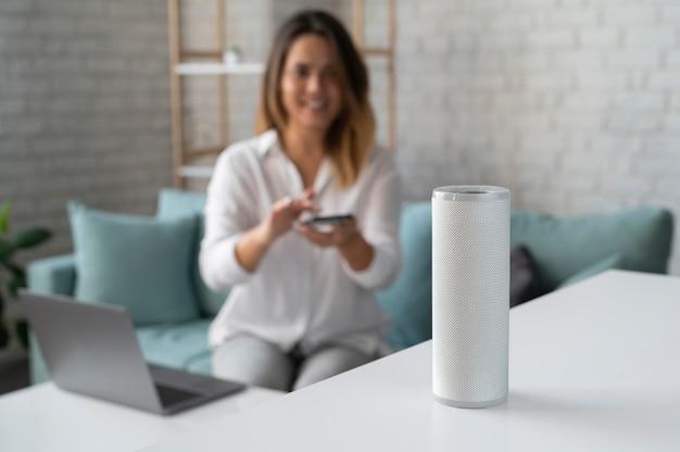 Frau mit digitalem lautsprecherassistenten