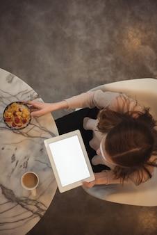 Frau mit digitaler tablette, die frühstück zu hause hat