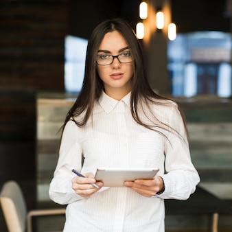 Frau mit digitaler tablette im café