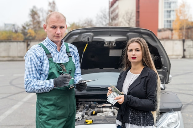 Frau mit dollar, der zum mechaniker für autoservice zahlt