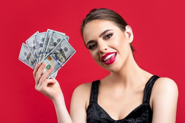 Frau mit dollar in der hand. porträtfrau, die geldbanknoten hält. mädchen, das bargeld in dollarbanknoten hält. frau, die viel geld in dollar-währung hält. luxus-, schönheits- und geldkonzept.