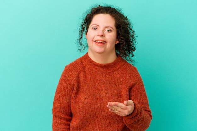 Frau mit down-syndrom, die hand in der grußgeste streckt.