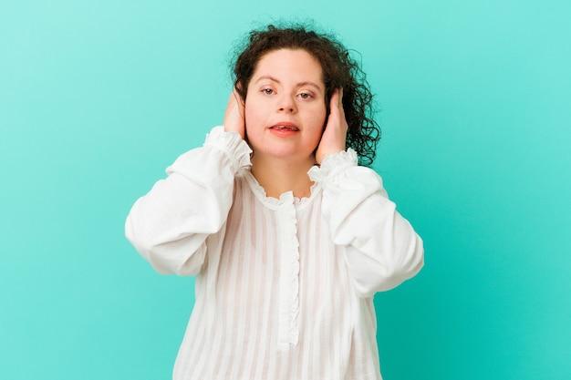 Frau mit down-syndrom isoliert die ohren mit den händen.