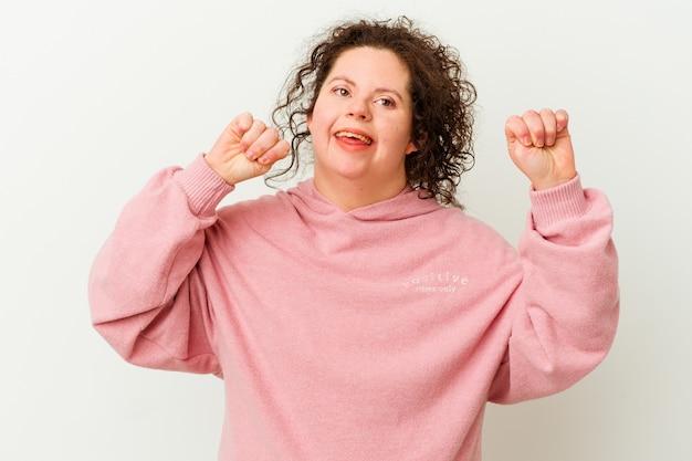 Frau mit down-syndrom isoliert feiert einen besonderen tag, springt und hebt die arme mit energie