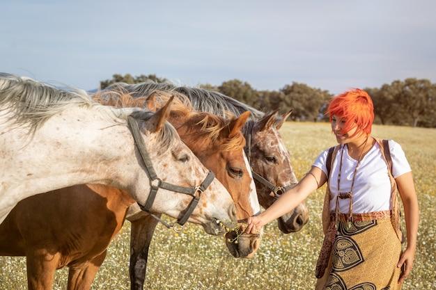 Frau mit drei pferden auf dem lande
