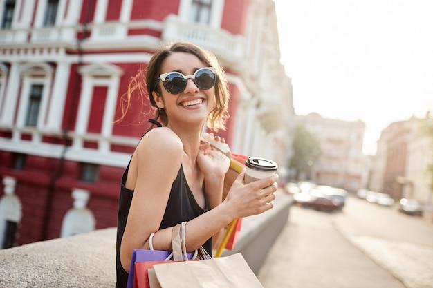 Frau mit dunklem haar in sonnenbrille und schwarzem kleid, das hell lächelt