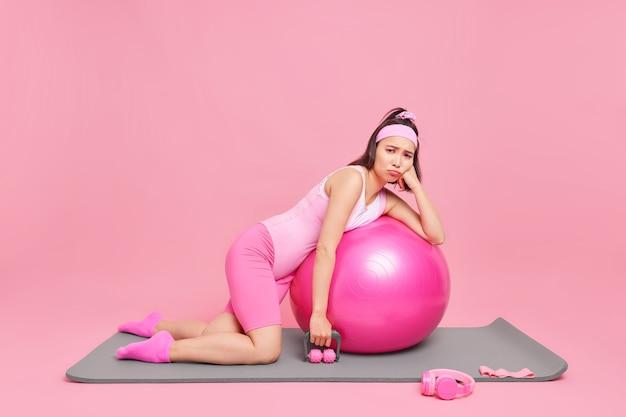Frau mit dunklen haaren lehnt sich an fitball-posen auf fitnessmatte in activewear hat niedergeschlagenen gesichtsausdruck geht in innenräumen zum sport hat keine motivation.