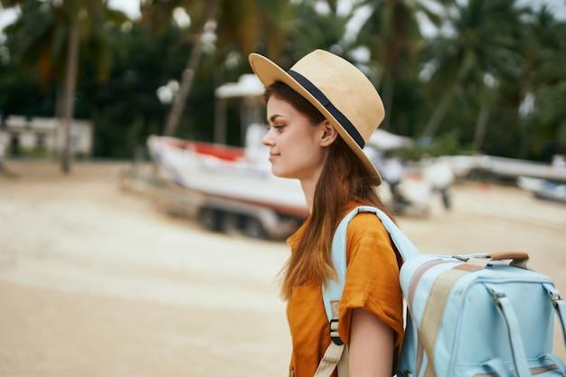 Frau mit einem blauen rucksack in einem gelben kleid und hut geht entlang des ozeans entlang des sandes mit palmen