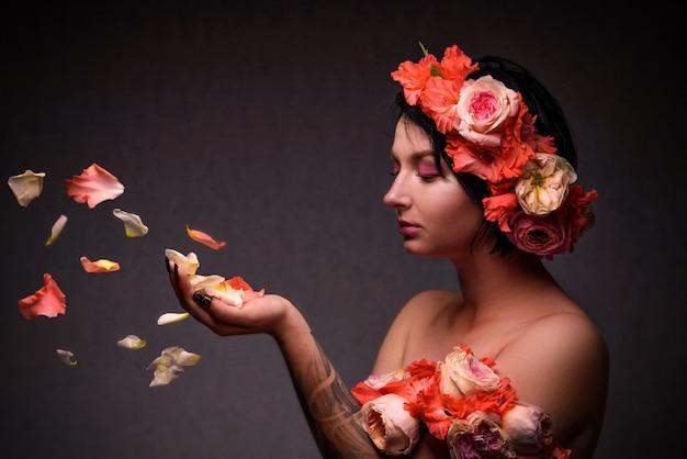 Frau mit einem blumenkranz und rosafarbenen blumenblättern in ihren händen
