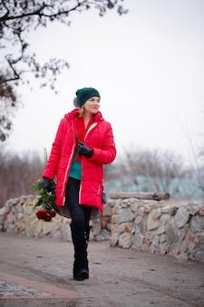 Frau mit einem blumenstrauß geht die straße entlang