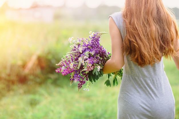 Frau mit einem blumenstrauß von lupine blüht an einem sonnigen sommertag
