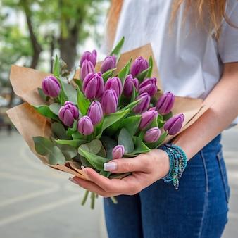 Frau mit einem blumenstrauß von violetten tulpen.