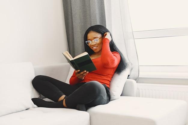 Frau mit einem buch auf dem sofa