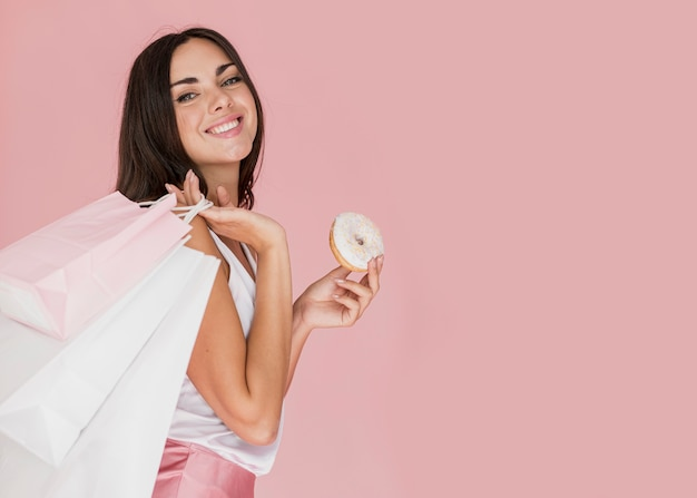 Frau mit einem donut mit weißer schokolade und einkaufsnetzen