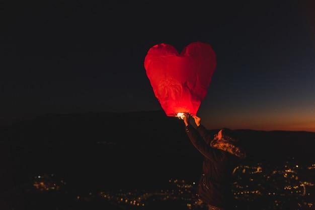 Frau mit einem drachen von heißer luft in der nacht