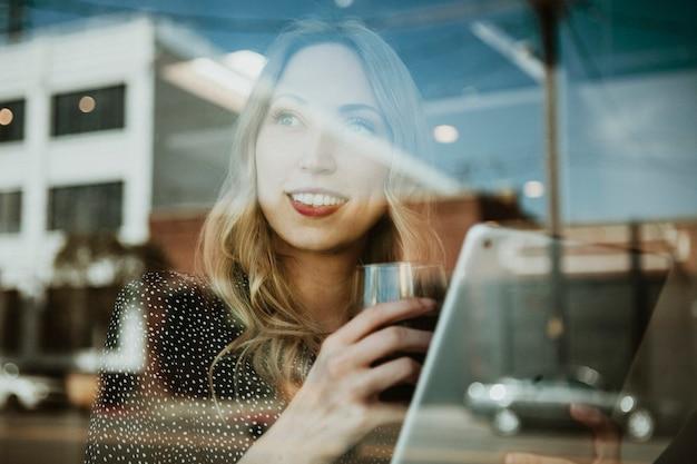 Frau mit einem drink mit einem digitalen tablet