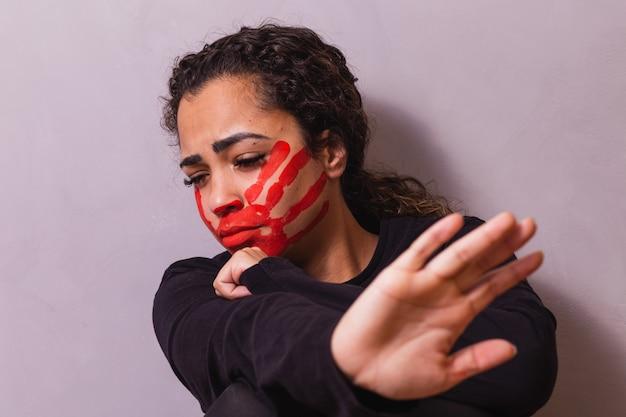 Frau mit einem druck auf dem mund, der gewalt gegen frauen demonstriert. frau protestiert gegen häusliche gewalt und missbrauch im hintergrund.