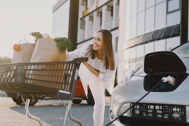 Frau mit einem einkaufswagen, der elektroauto an der elektrischen tankstelle auflädt