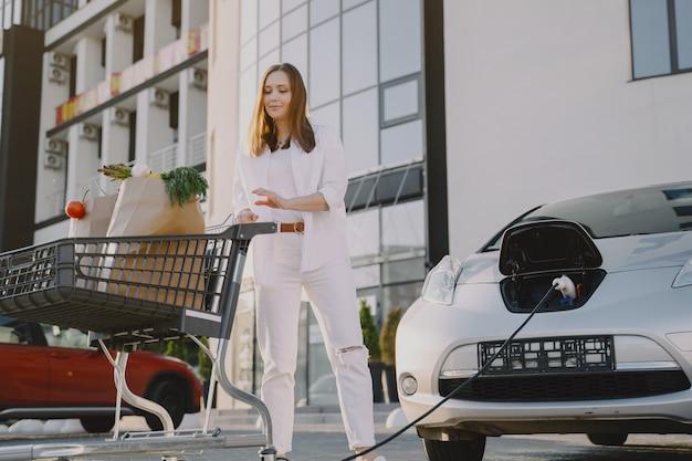 Frau mit einem einkaufswagen durch ihr auto
