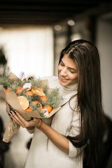 Frau mit einem fruchtblumenstrauß auf weihnachten