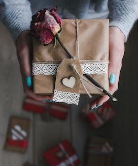 Frau mit einem geschenk und einer trockenen rose