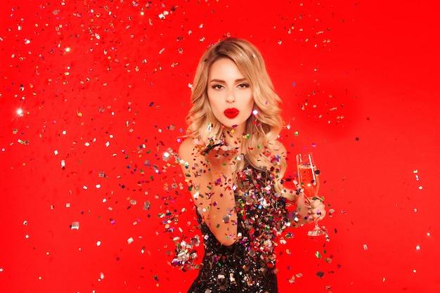 Frau mit einem glas champagner party des neuen jahres feiernd. porträt des schönen lächelnden mädchens in glänzendem schwarzem kleiderwerfendem konfetti