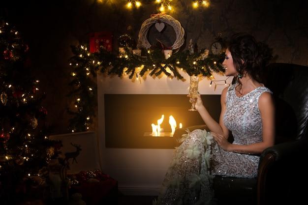 Frau mit einem glas champagner sitzend neben einem kamin