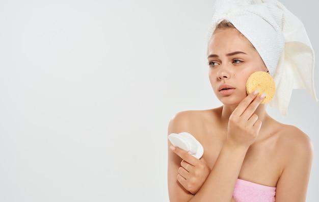 Frau mit einem handtuch auf dem kopf hält einen schwamm in ihrem handkosmetikdermatologiemodell.