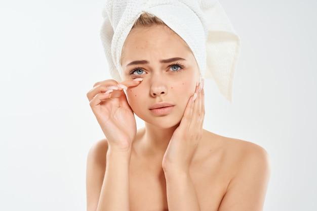 Frau mit einem handtuch auf dem kopf hautpflege gesicht dermatologie hygiene